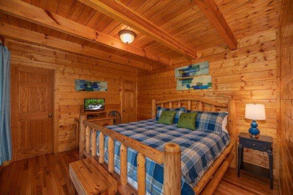 Log bed, night stand with lamp, and TV in a bedroom at Majestic Mountain, a 4 bedroom cabin rental located in Pigeon Forge