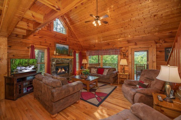 Living room with vaulted ceiling, fireplace, TV, and seating at Majestic Mountain, a 4 bedroom cabin rental located in Pigeon Forge