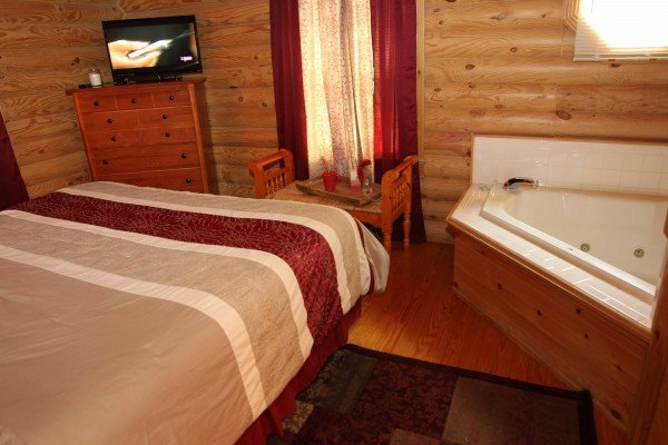 Bedroom with a TV, chest of drawers, bench, and jacuzzi at Kountry Lovin', a 2 bedroom cabin rental located in Pigeon Forge