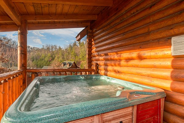Hot tub on a covered deck at Kountry Lovin', a 2 bedroom cabin rental located in Pigeon Forge