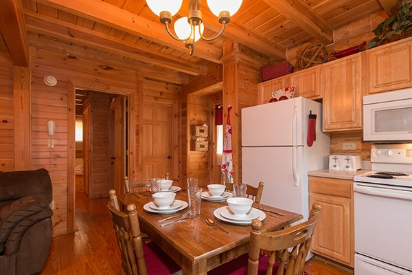 Kitchen with white appliances and dining space for four at Kountry Lovin', a 2 bedroom cabin rental located in Pigeon Forge