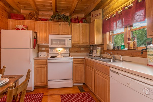 Kitchen with white appliances at Kountry Lovin', a 2 bedroom cabin rental located in Pigeon Forge