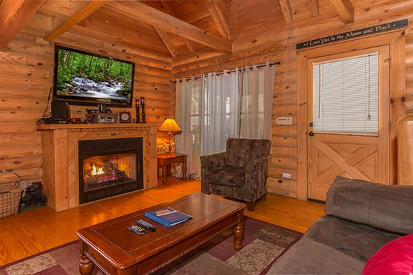 Living room with fireplace and tv at Kountry Lovin', a 2 bedroom cabin rental located in Pigeon Forge