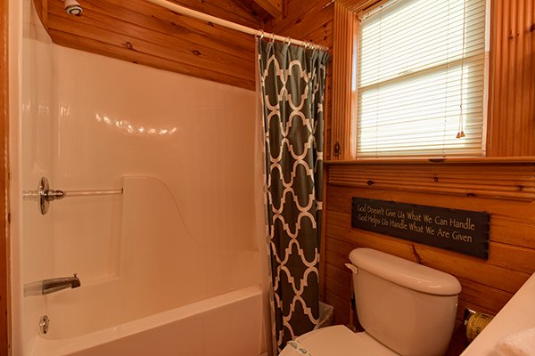 Bathroom with a tub and shower at Kountry Lovin', a 2 bedroom cabin rental located in Pigeon Forge