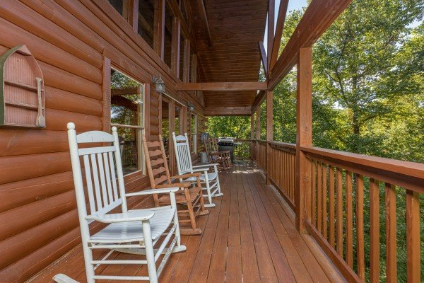 Rocking chairs on a covered deck at Highland Moose, a 2 bedroom cabin rental located in Pigeon Forge