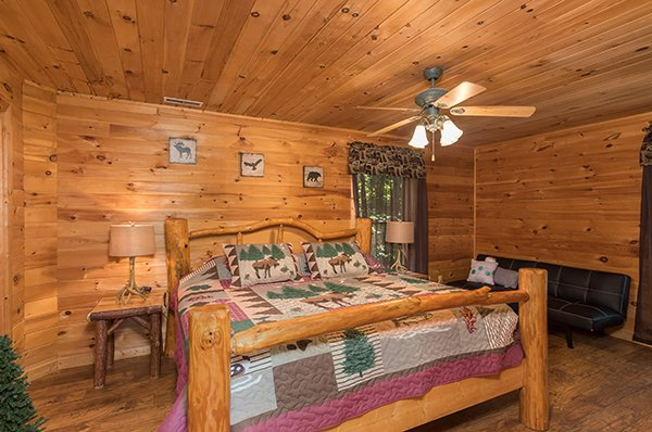Bedroom with a king log bed, end tables, and a bench seat at Highland Moose, a 2 bedroom cabin rental located in Pigeon Forge