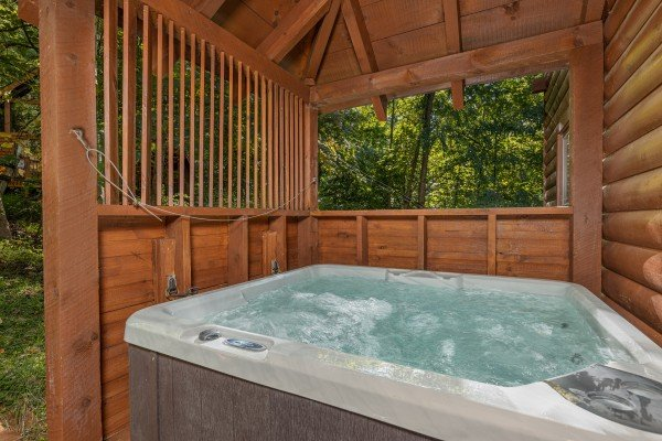 Hot tub on a covered deck at Highland Moose, a 2 bedroom cabin rental located in Pigeon Forge