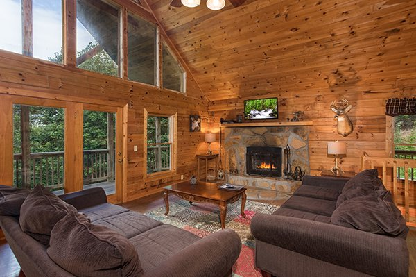 Living room with vaulted ceiling, fireplace, and TV at Highland Moose, a 2 bedroom cabin rental located in Pigeon Forge