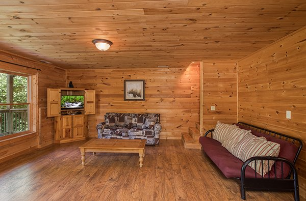 Living room off the game room with a sleeper sofa and futon at Highland Moose, a 2 bedroom cabin rental located in Pigeon Forge