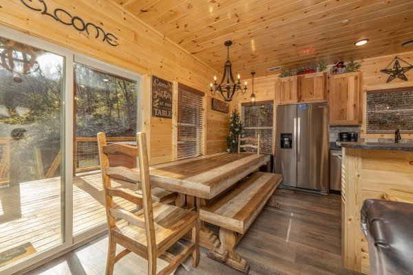 Dining table with chairs and benches at Wet Feet Retreat, a 5 bedroom cabin rental located in Pigeon Forge