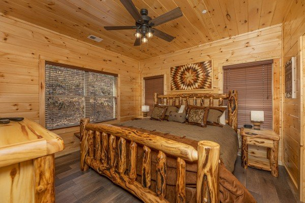 Bedroom with a king log bed, two night stands, and lamps at Wet Feet Retreat, a 5 bedroom cabin rental located in Pigeon Forge