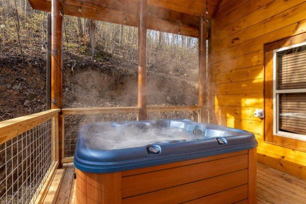 Hot tub on a covered deck at Wet Feet Retreat, a 5 bedroom cabin rental located in Pigeon Forge