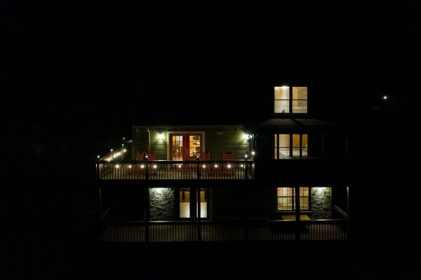 View of rear exterior lit at night at Wonders in the Sky, a 3 bedroom cabin rental located in Gatlinburg
