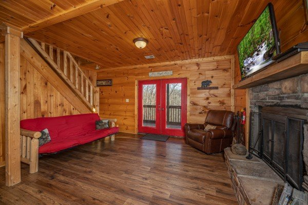 Futon, fireplace, TV, and deck access at Wonders in the Sky, a 3 bedroom cabin rental located in Gatlinburg