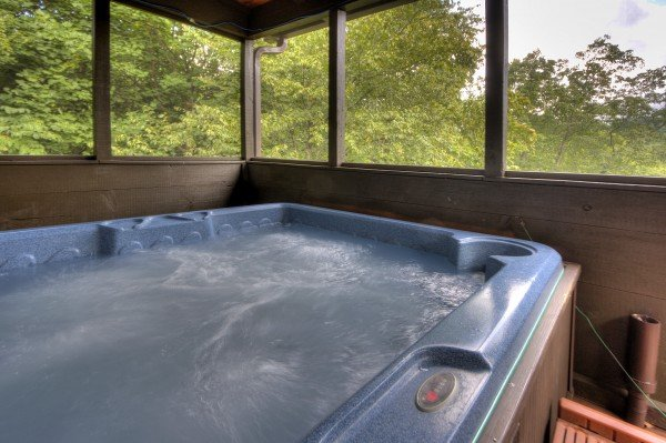 Hot tub on a covered deck at Wonders in the Sky, a 3 bedroom cabin rental located in Gatlinburg