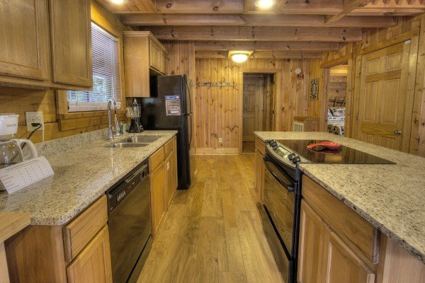 Kitchen with granite counters and black appliances at Wonders in the Sky, a 3 bedroom cabin rental located in Gatlinburg