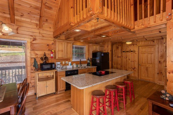 Kitchen with black appliances and counter seating for four at Wonders in the Sky, a 3 bedroom cabin rental located in Gatlinburg