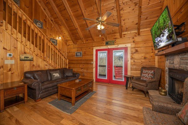 Living room with sofa, TV, fireplace, and deck access at Wonders in the Sky, a 3 bedroom cabin rental located in Gatlinburg