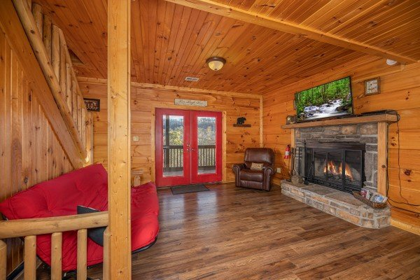 Lower living room with futon, fireplace, TV, and deck access at Wonders in the Sky, a 3 bedroom cabin rental located in Gatlinburg