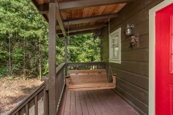 Swing on a covered porch at Wonders in the Sky, a 3 bedroom cabin rental located in Gatlinburg