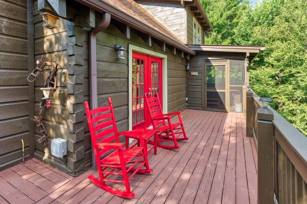 Red rocking chairs on the deck at Wonders in the Sky, a 3 bedroom cabin rental located in Gatlinburg