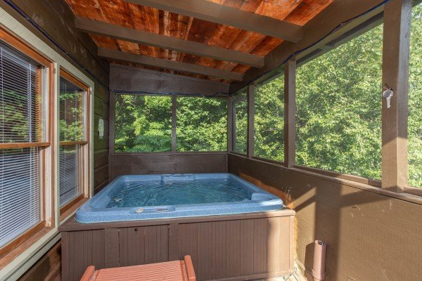 Hot tub on a screened porch at Wonders in the Sky, a 3 bedroom cabin rental located in Gatlinburg
