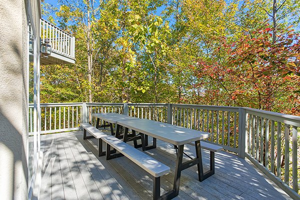 Picnic table on the deck surrounded by fall trees at The Majestic, an 8 bedroom cabin rental located in Gatlinburg
