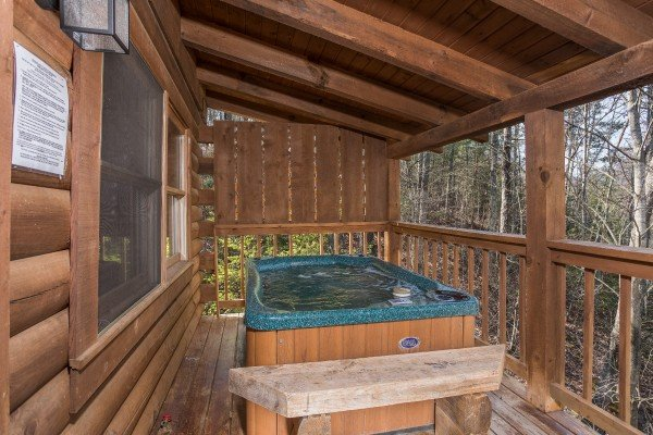 Hot tub on a covered porch with privacy fence at Makin Memories, a 1 bedroom cabin rental located in Pigeon Forge