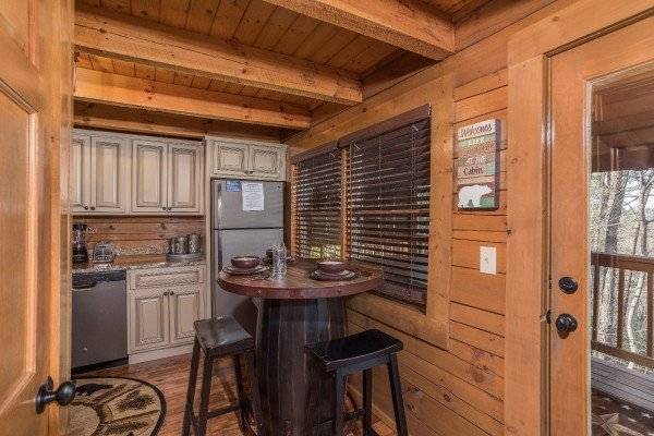 Kitchen with high top table with seating for two at Makin Memories, a 1 bedroom cabin rental located in Pigeon Forge
