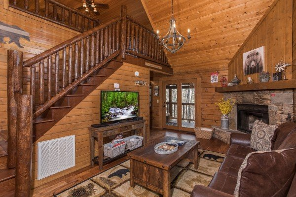 Living room with a TV, fireplace, and vaulted ceiling at Makin Memories, a 1 bedroom cabin rental located in Pigeon Forge