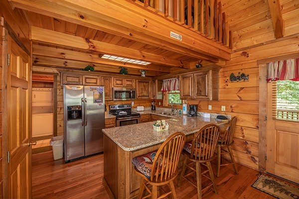 Breakfast bar with granite counters and stainless appliances at Eagles View Lodge, a 3 bedroom cabin rental located in Gatlinburg