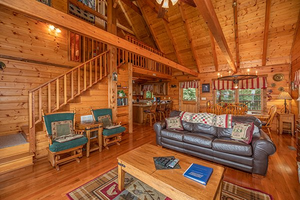 Two gliders and a sofa in the open living room at Eagles View Lodge, a 3 bedroom cabin rental located in Gatlinburg