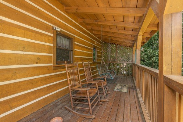 Rocking chairs and a swing on a deck at Eagles View Lodge, a 3 bedroom cabin rental located in Gatlinburg