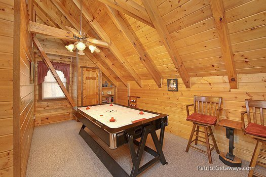 Pool and air hockey two-in-one table in the lofted game room at Eagle's View Lodge, a 3-bedroom cabin rental located in Gatlinburg