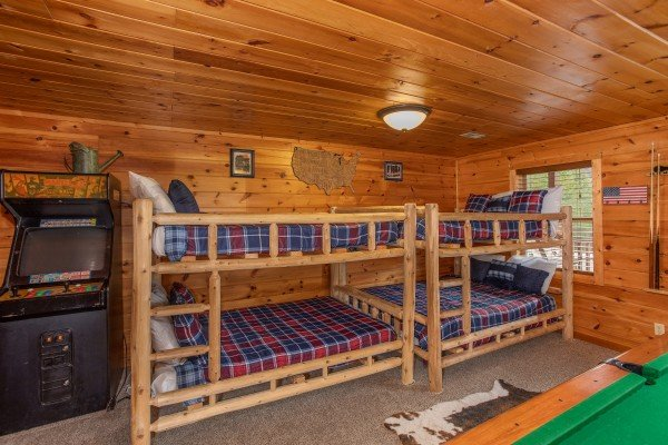 Two sets of full-sized bunk beds in the game room at Hibernation Station, a 3-bedroom cabin rental located in Pigeon Forge