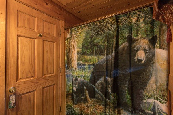 Bathroom with a tub and shower and black bear decor at Hibernation Station, a 3-bedroom cabin rental located in Pigeon Forge