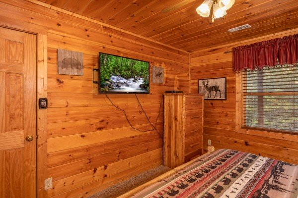 King bedroom with a TV and dresser at Hibernation Station, a 3-bedroom cabin rental located in Pigeon Forge