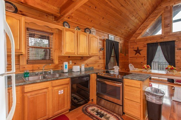 Kitchen with counter top seating and a dining space for six at Hibernation Station, a 3-bedroom cabin rental located in Pigeon Forge