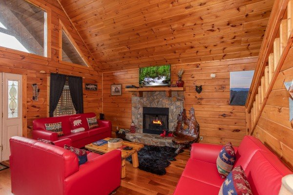 Living room with a sofa, loveseat, chair, fireplace, and Smart TV at Hibernation Station, a 3-bedroom cabin rental located in Pigeon Forge