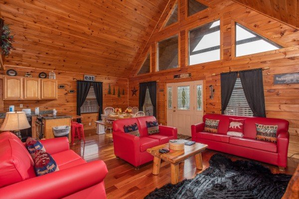 Living room with vaulted ceiling, looking into the dining room and kitchen at Hibernation Station, a 3-bedroom cabin rental located in Pigeon Forge