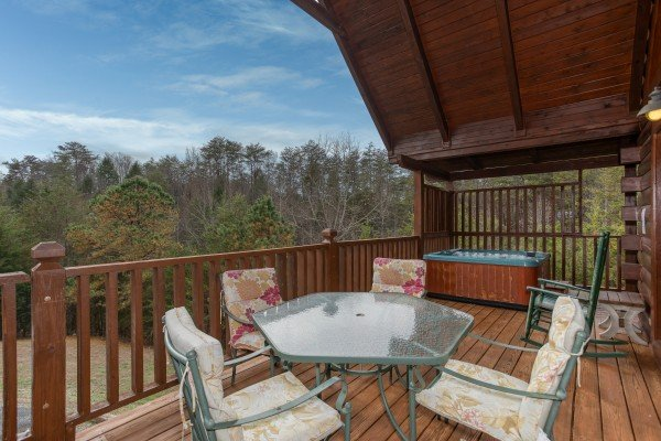 Covered deck with dining table for four at Hibernation Station, a 3-bedroom cabin rental located in Pigeon Forge