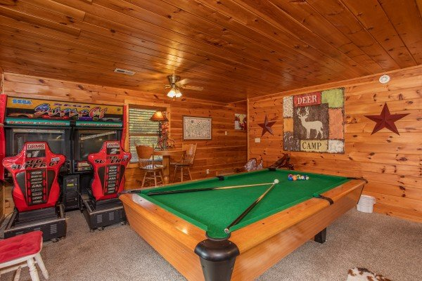 Pool table and driving arcade game in the game room at Hibernation Station, a 3-bedroom cabin rental located in Pigeon Forge