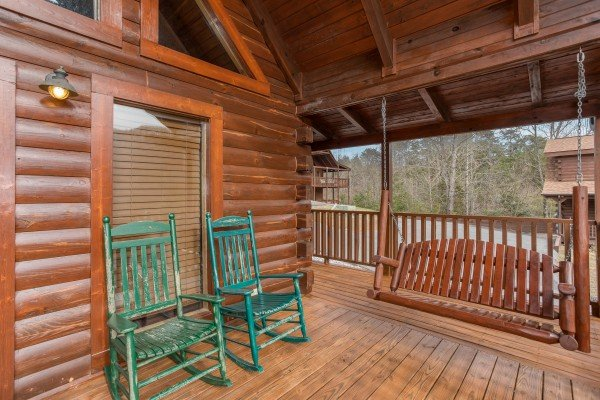 Swing and rocking chairs on the covered deck at Hibernation Station, a 3-bedroom cabin rental located in Pigeon Forge