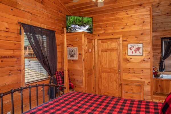 Bedroom with a television and in-room jacuzzi at Hibernation Station, a 3-bedroom cabin rental located in Pigeon Forge