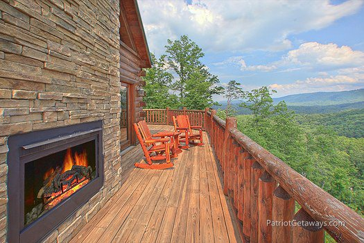 Deck with fireplace and rocking chairs at Majestic Views, a 3 bedroom cabin rental located in Pigeon Forge