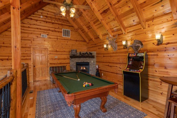 Game loft with a pool table, arcade game, and fireplace at Majestic Views, a 3 bedroom cabin rental located in Pigeon Forge