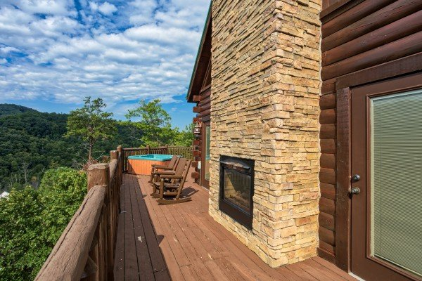 Hot tub and rocking chairs on a deck with an outdoor fireplace at Majestic Views, a 3 bedroom cabin rental located in Pigeon Forge