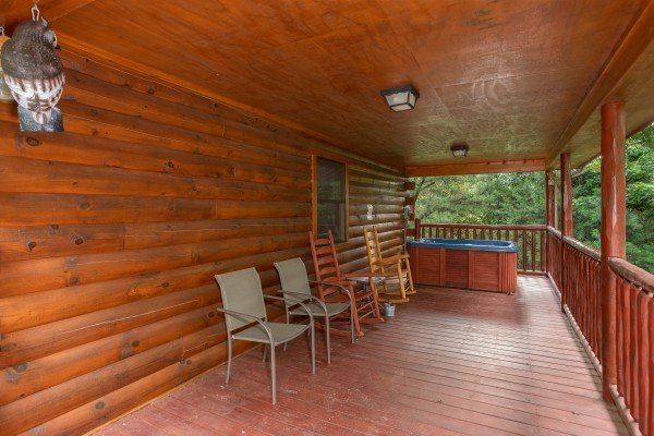 Covered deck with two chairs, two rocking chairs, and a hot tub at Can't Bear to Leave, a 1-bedroom cabin rental located in Gatlinburg