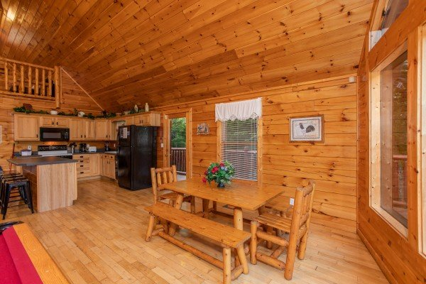 Dining table with two chairs and two long benches in the open concept room at Can't Bear to Leave, a 1-bedroom cabin rental located in Gatlinburg