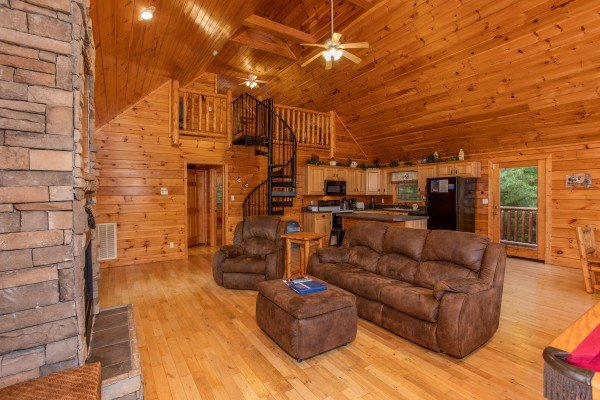 Sofa, recliner, and ottoman facing the fireplace in the grand living room at Can't Bear to Leave, a 1-bedroom cabin rental located in Gatlinburg